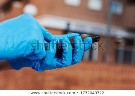 man wearing latex gloves using his smartphone Stock photo © nito