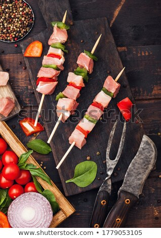 Raw pork kebab with paprika on chopping board with fresh vegetables on wooden background with fork a Stock photo © DenisMArt