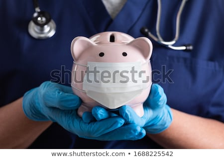 Foto stock: Doctor Holding Stethoscope To Piggy Bank