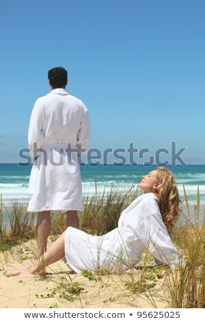 Husband and wife on the beach in bath robes Stock photo © photography33