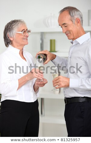 mature man pouring sparkling wine to his wife Stock photo © photography33