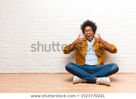 casual man sitting thumbs up stock photo © feedough