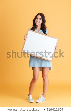 lovely young woman holding empty white board stock photo © acidgrey
