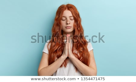 portrait of young woman standing in praying position stock photo © wavebreak_media