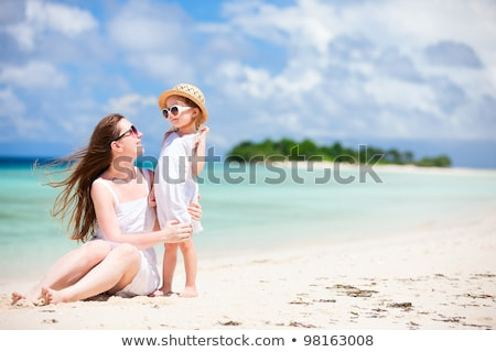 Young beautiful mother and her adorable little daughter at tropical beach stock photo © travnikovstudio