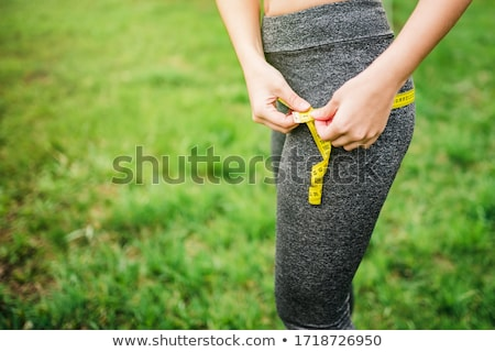 Jeune femme cuisse régime alimentaire mètre à ruban femme Photo stock © Kzenon