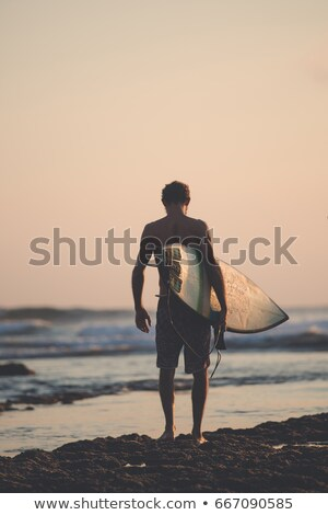 surfer walking to the ocean for a sunset ride stock photo © jeffbanke