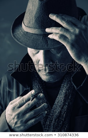 man looking down while holding a cigarette in his hand stock photo © feedough