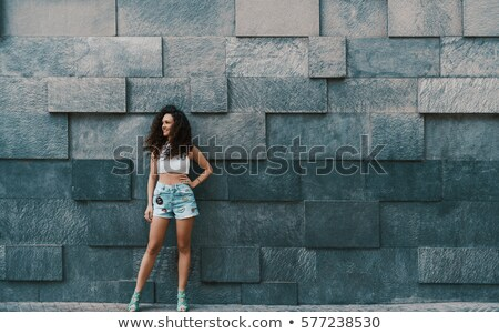 брюнетка · каменной · стеной · сидят · женщину · девушки - Сток-фото © acidgrey