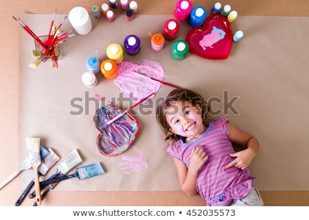 playful little girl surrounded by her paints stock photo © ozgur