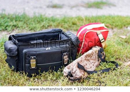 Red travelling suitcase and camera tripod Stock photo © nalinratphi