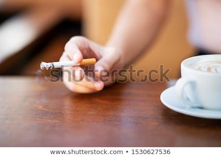 Jeune femme fumer cigarette café séance Photo stock © deandrobot