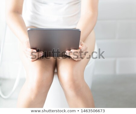 Stock photo: Woman with the tablet pc in a toilet