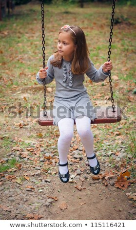 Young girl sitting on a swing in a park Stock photo © IS2