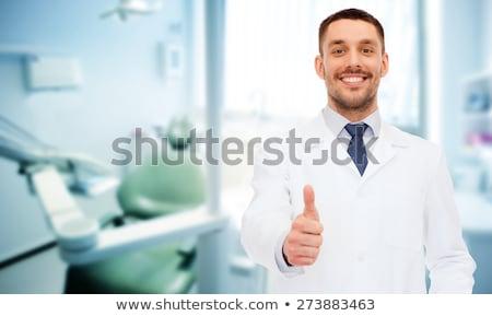 dentist at dental clinic showing thumbs up stock photo © dolgachov