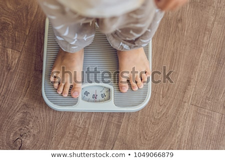 The boy stands on the scales to find out his weight Stock photo © galitskaya