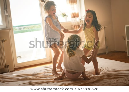 three little sisters jumping on a bed stock photo © dashapetrenko