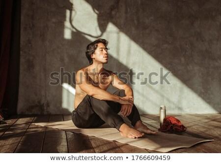 portrait of a calm sportsman sitting on a fitness mat stock photo © deandrobot