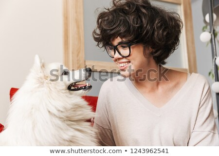 Curly woman sitting on sofa with her cutie white dog. Stock photo © deandrobot