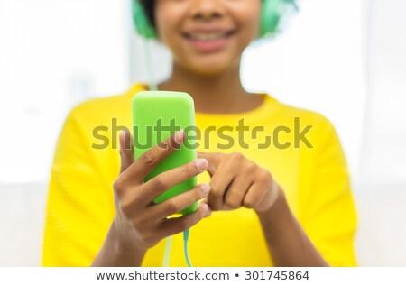 közelkép · mosolyog · fiatal · lány · zenét · hallgat · fülhallgató · pihen - stock fotó © dolgachov