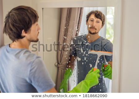 Young man cleaning mirror at home hotel Stock photo © Elnur