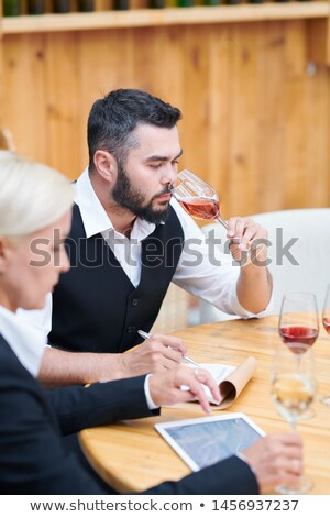 Bearded young man in formalwear smelling various sorts of wine Stock photo © pressmaster