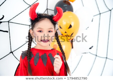 Pretty girl in devil costume smiling stock photo © nyul