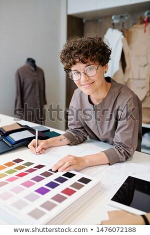 Fiatal designer készít jegyzetek néz iktatókönyv Stock fotó © pressmaster