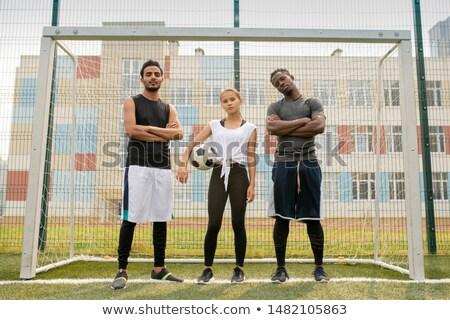 College soccer team consisting of intercultural guys and Caucasian girl Stock photo © pressmaster