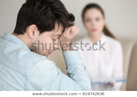 Man patient having a migraine headache and female doctor in the  Stock photo © Freedomz