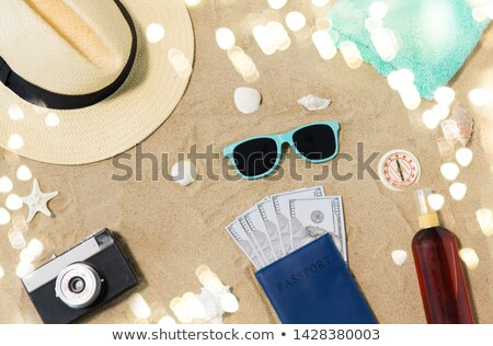 money in passport, shades and hat on beach sand Stock photo © dolgachov