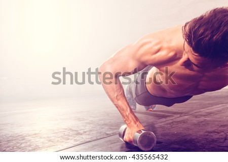 Image of handsome athletic man doing exercise with dumbbells Stock photo © deandrobot