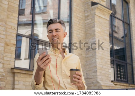 Image of confident businessman using cellphone and earphones Stock photo © deandrobot