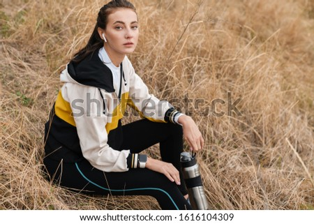 Photo of nice brunette woman using earpods and holding water bottle Stock photo © deandrobot
