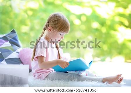 Cute little girl reading book at home, at windowsill Stock photo © Illia