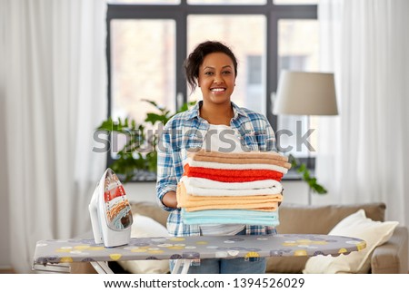 african american woman with ironed linen at home Stock photo © dolgachov