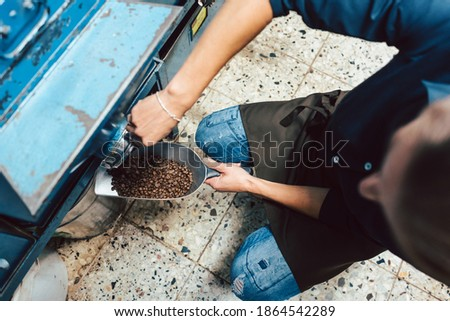 Woman taking coffee beans out of the storage Stock photo © Kzenon