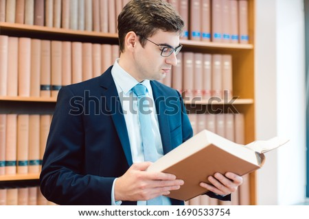 Lawyer in his office reading precedents in thick books Stock photo © Kzenon