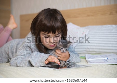 7 years old girl with kitten at home bed Stock photo © Lopolo