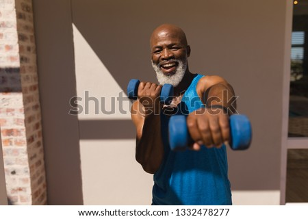 Front view of determined senior African American man exercising with kettle bells standing in the fi Stock photo © wavebreak_media