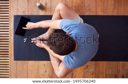man with tablet computer meditating at home Stock photo © dolgachov