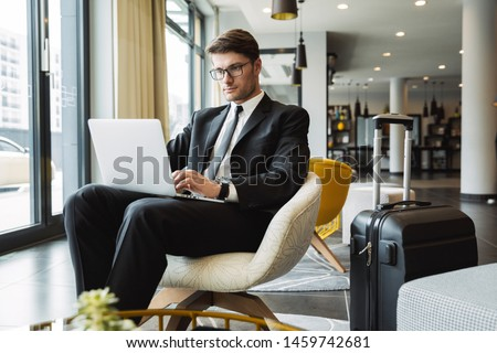 Photo of business man wearing eyeglasses sitting in armchair, an Stock photo © deandrobot