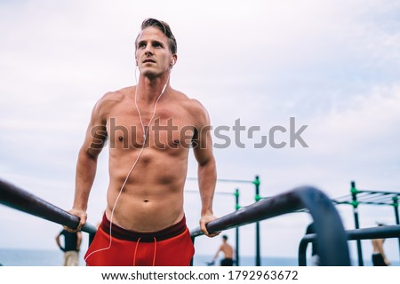 Serious, determined and motivated handsome sportsman using orange resistance band, stretch it in han Stock photo © benzoix