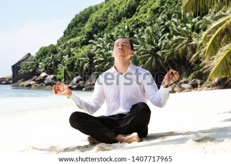 Man In Formalwear Sitting On The Beach Mediating Stock photo © AndreyPopov