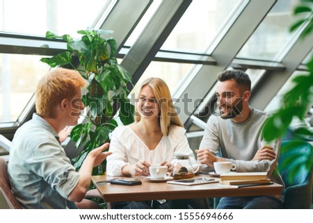 Group of cheerful students relaxing in cafe after classes and having tea Stock photo © pressmaster