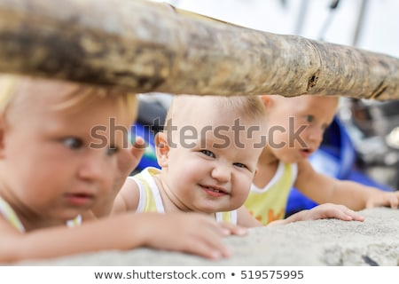 Three baby Toddler looking through fence on the hens and roosters in the henhouse. The yellow shirts Stock photo © galitskaya