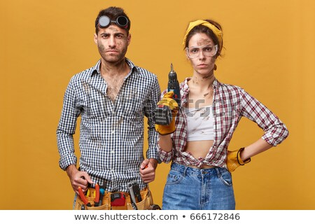 Serious young technician in workwear doing repair work with electric drill Stock photo © pressmaster