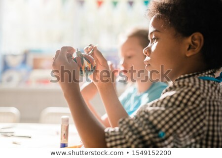 cute african schoolboy holding handmade decorative christmas toy ball stock photo © pressmaster