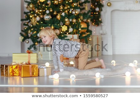 The boy has fun and fools around a new year tree with gifts at home Stock photo © ElenaBatkova