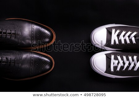 Mixed shoes. Oxford and sneakers shoe on black background.  Different style of men fashion. Compare  Stock photo © Illia